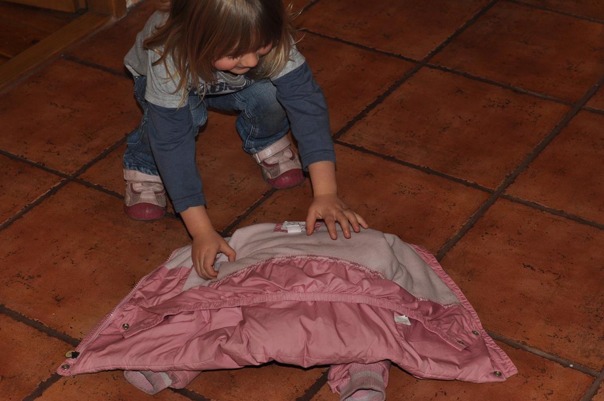 Dwulatek zakłada kurtkę